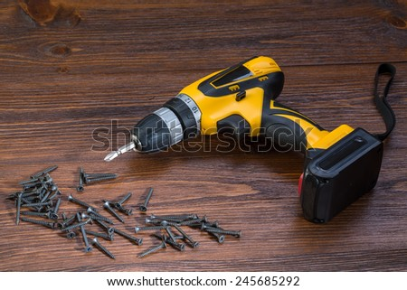 electric screwdriver on a wooden background - stock photo