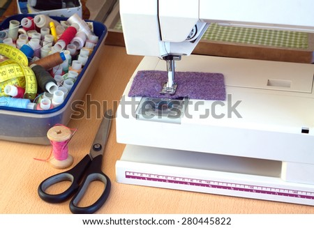Electric sewing machine and sewing accessories: scissors, color spools with  thread and cloth closeup - stock photo