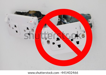 electric sockets installation in white walls at house construction site with prohibit sign - stock photo