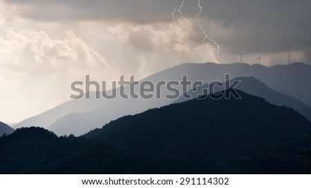 Electric storm over wind farm, turbines. Green energy.  - stock photo