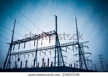 electric substation silhouetted against blue sky at dusk  - stock photo
