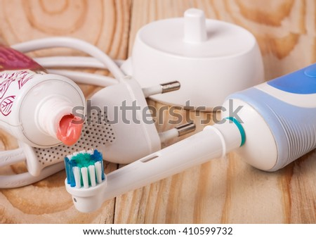 electric toothbrush with a tube of toothpaste on  wooden background - stock photo