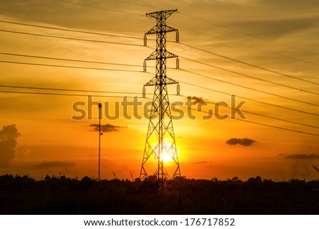 Electric transmission tower with sunset blackground. - stock photo