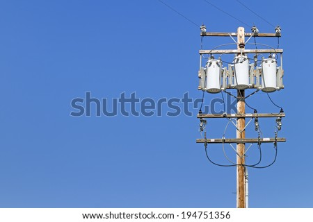 Electric utility pole with 3 transformers. Wooden post with high voltage signs, power distribution lines. Room for text, copy space. Blue sky background.  - stock photo
