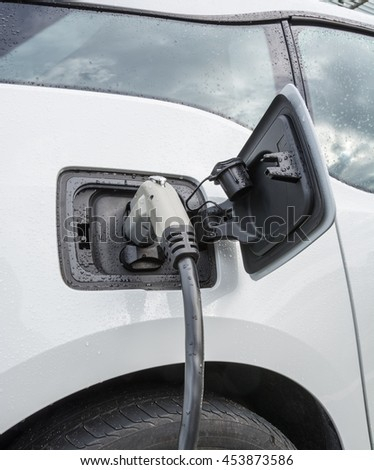 Electric vehicle charging. Charging port of electric car. Charging an electric car with the power supply plugged in. - stock photo