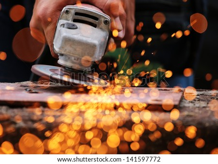 Electric wheel grinding on steel structure - stock photo