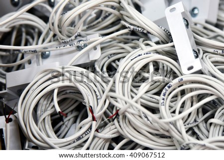 Electric white cable. Wire wound into skeins and rings. Electric wire cable product.  Connect the source of electric current with the consumer, components of the electrical circuit. Industrial details - stock photo