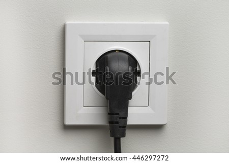 Electric white socket and one plugged in power cord on white wall background - stock photo