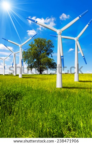 Electric Wind Generators in Countryside. Five wind turbines in countryside with tree, blue sky, clouds and sun rays - stock photo