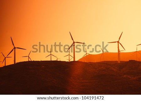 Electric wind turbines farm silhouettes on sun background - stock photo