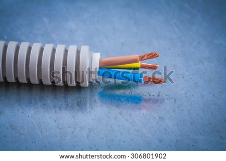 Electric wire protection and copper cables on scratched metallic background. - stock photo