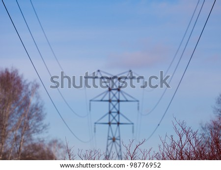 Electric wires on blue sky and forest - stock photo