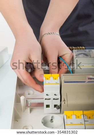 electrical appliance repairs. electrician fixing cable in domestic electrical box - stock photo