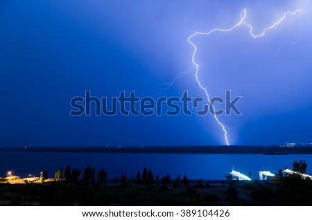 Electrical discharges of lightning in the night sky above the river
