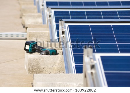 Electrical drill or borer by the solar panel flat roof construction  - stock photo