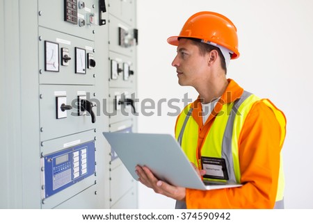 electrical engineer with laptop computer in power plant control room - stock photo