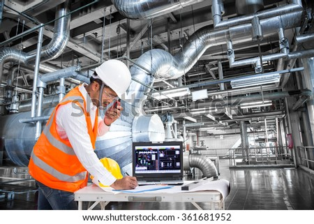 Electrical engineer working at control room of a modern thermal power plant - stock photo
