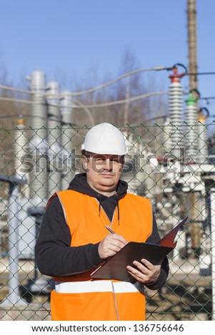Electrical engineer written documentation near to the electric substations - stock photo