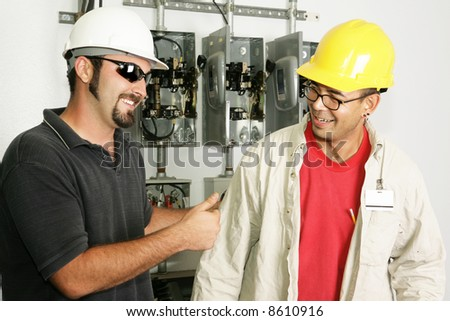 Electrical foreman giving a worker the thumbs-up. Models are actual electricians.