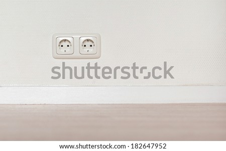Electrical jack white plastic socket on a white wall - stock photo