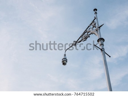 Electrical lamp is hanging on the classical metal pole in the evening time.