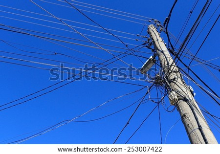 Electrical old wooden powerlines with blue sky - stock photo
