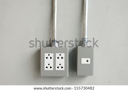 electrical outlet and light switches on cement wall - stock photo