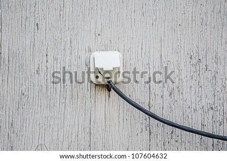 electrical outlet with a wire on an old wall
