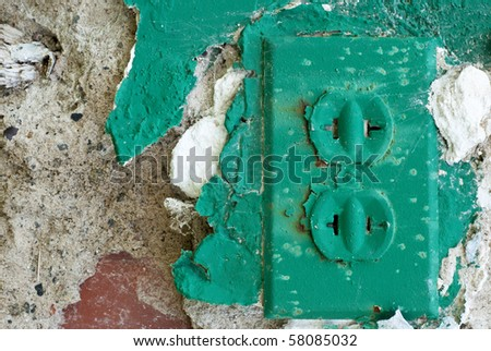 electrical outlet with green chipped paint in an old abandoned environment