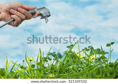Electrical plug watering a green grass meadow as a symbol of green and renewable energy - stock photo