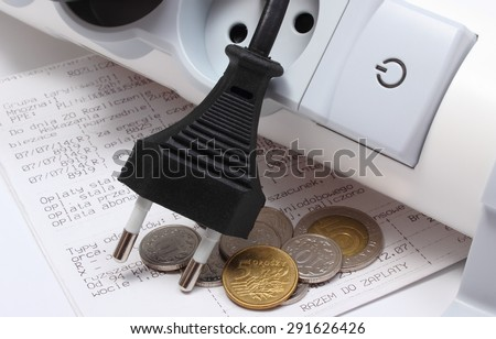 Electrical plugs with cords disconnected from electrical power strip, electricity bill with heap of coins, concept of energy saving - stock photo