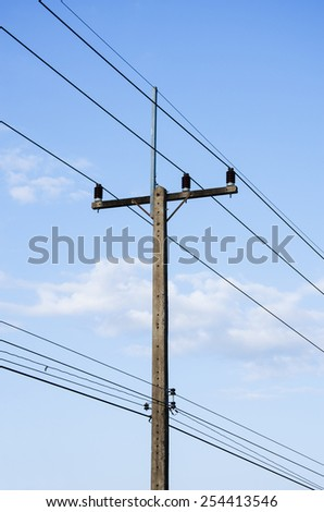 electrical post by the road against blue sky - stock photo