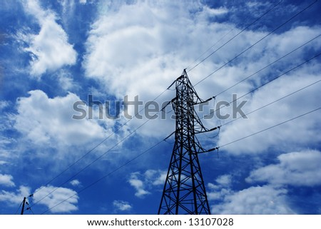 Electrical power lines against blue cloudy sky