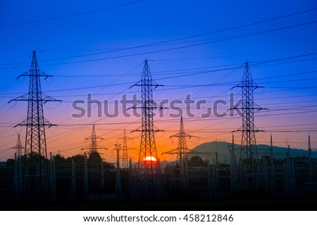 Electrical power lines and pylons against vibrant colorful sunset with blue and orange sky.