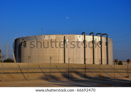 Electrical power plant storage tank against blue sky
