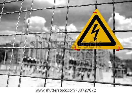 Electrical power plant with High Voltage sign in a fence - stock photo