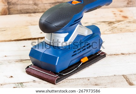 Electrical sander tool on wooden background. - stock photo