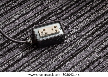 Electrical socket with power plug cable on carpet floor for safety concept - stock photo