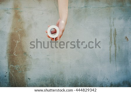 Electrical tape in hand on background concrete table