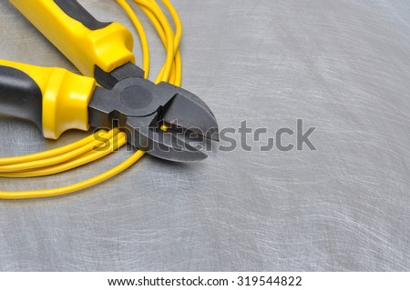 Electrical tools and cables on metal surface with place for text - stock photo