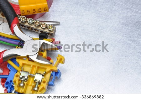 Electrical tools and component kit to use in electrical installations on grey metal background with place for text - stock photo