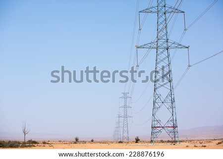 Electrical towers across a desert background and blue sky near Tata, in the hottest region of Morocco in 2014.