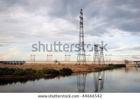 Electrical towers on river bank - stock photo