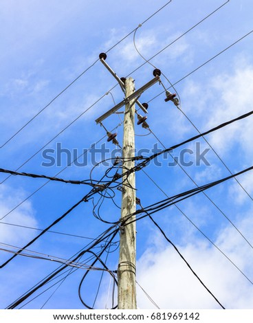 Electrical Wires And Internet Cables Connected To Passing By A Tall Wooden Power Pole