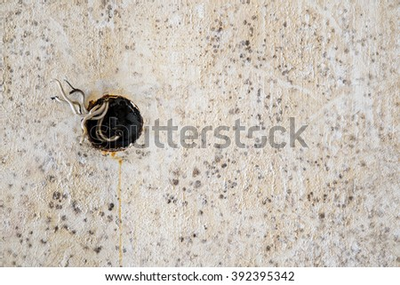 Electrical wires sticking out from electrical socket hole on beige color concrete wall - stock photo