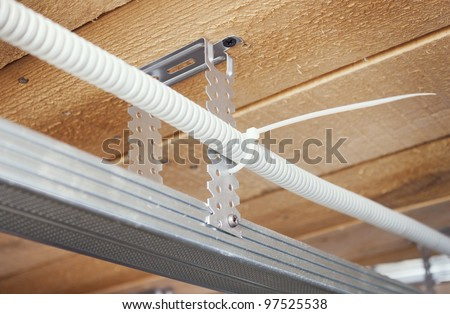 Electrical wiring is laid in a suspended ceiling