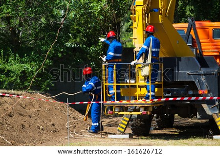 Electrical workers on the lift. Repairing lines - stock photo