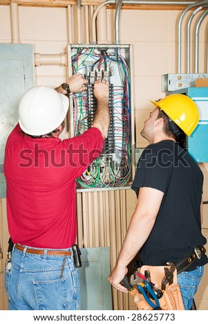 Electrician and apprentice changing out a faulty circuit breaker in an industrial panel. - stock photo