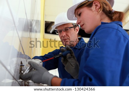 Electrician and his apprentice - stock photo