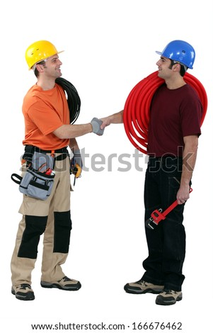 Electrician and plumber shaking hands - stock photo